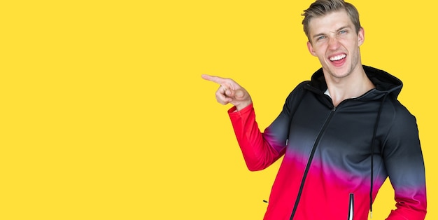 Chico joven de apariencia europea sobre fondo amarillo. señalar con el dedo un lugar vacío. copia espacio