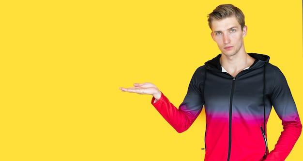 Chico joven de apariencia europea sobre fondo amarillo. sostiene una palma abierta vacía. copia espacio