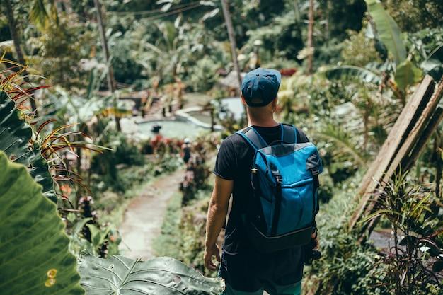 Chico joven con barba y una mochila posando en la selva con una gorra
