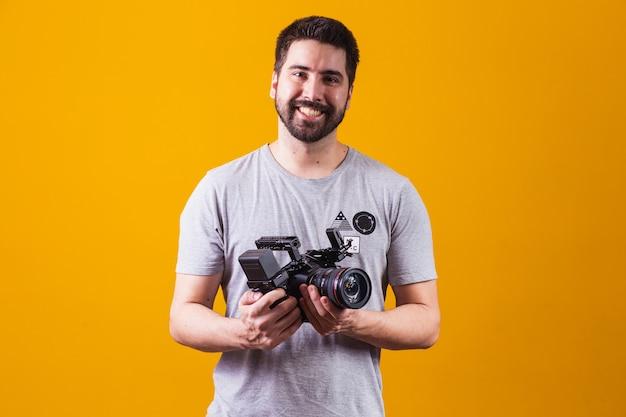 Chico joven con una cámara cinematográfica. director de cine