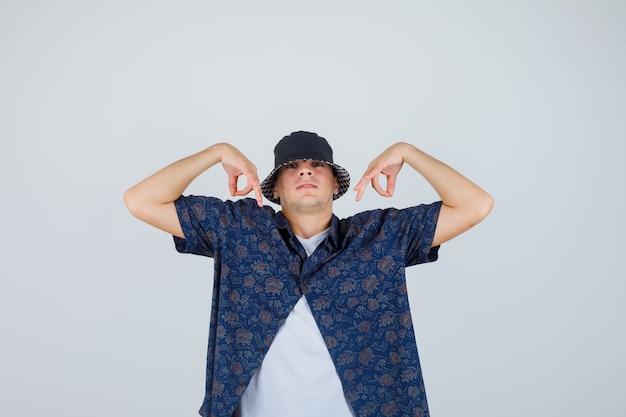 Chico joven en camiseta blanca, camisa floral, gorra mostrando signos de ok y mirando confiado, vista frontal.