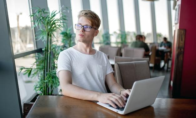 Chico joven con una camiseta blanca y gafas trabaja en un portátil sentado en una mesa en una cafetería