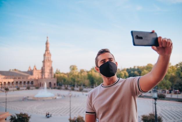 Chico joven caucásico con mascarilla tomando un selfie con su teléfono móvil en la plaza de españa en sevilla, españa. copie el espacio.