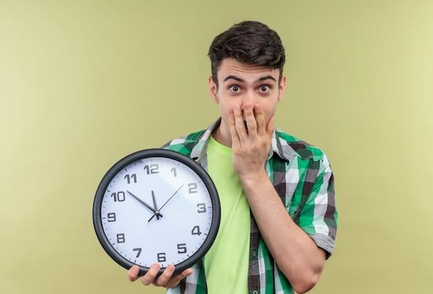 Chico joven caucásico sorprendido vistiendo camisa verde sosteniendo el reloj de pared con la boca cubierta con la mano sobre fondo verde aislado