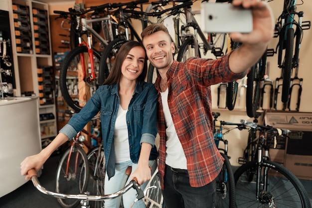 Un chico joven y una chica hacen un selfie en una tienda de bicicletas.
