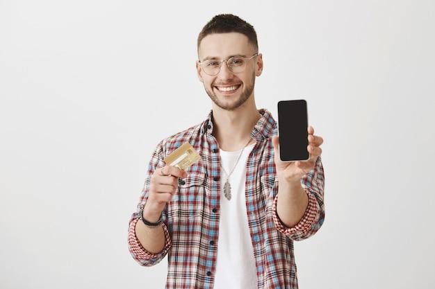 Chico joven complacido con gafas posando con su teléfono y tarjeta