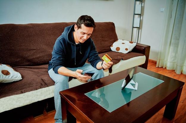 Chico joven comprando videojuegos por internet con su teléfono móvil