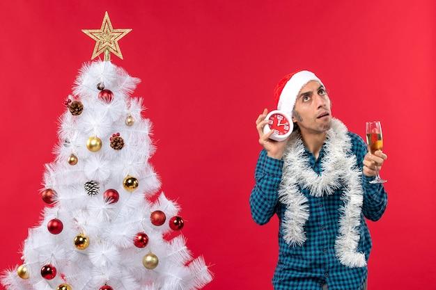 Chico joven confundido con sombrero de santa claus y sosteniendo una copa de vino y reloj de pie cerca del árbol de navidad