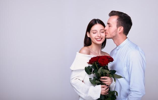 Un chico joven le da rosas a su bella novia y la besa.