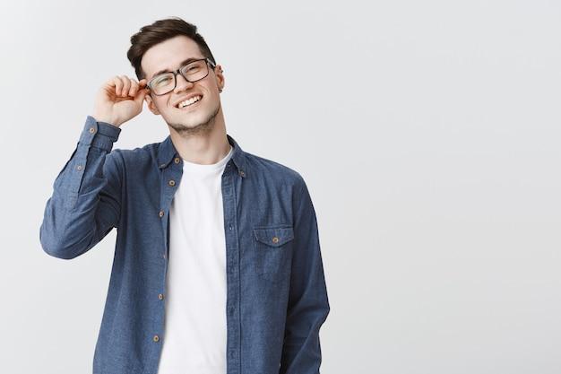Chico joven despreocupado sonriendo, ponerse gafas