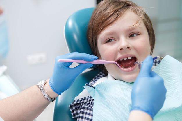 Chico joven divertido lindo mirando a su dentista mientras le examinan los dientes