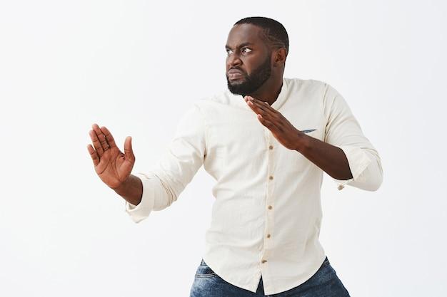 Chico joven enojado posando contra la pared blanca
