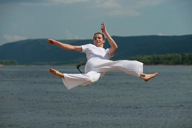 Chico joven entrena capoeira en el cielo