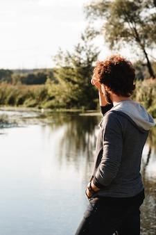Chico joven con estilo disfrutando del paisaje de la naturaleza tranquila.