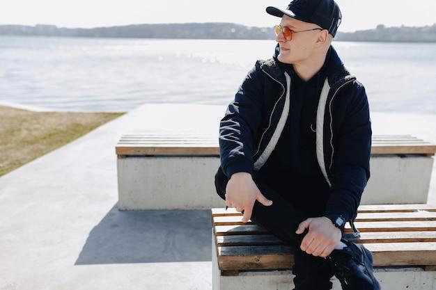 Chico joven con estilo en lentes naranjas, chaqueta y gorra, camina alrededor del lago en primavera u otoño