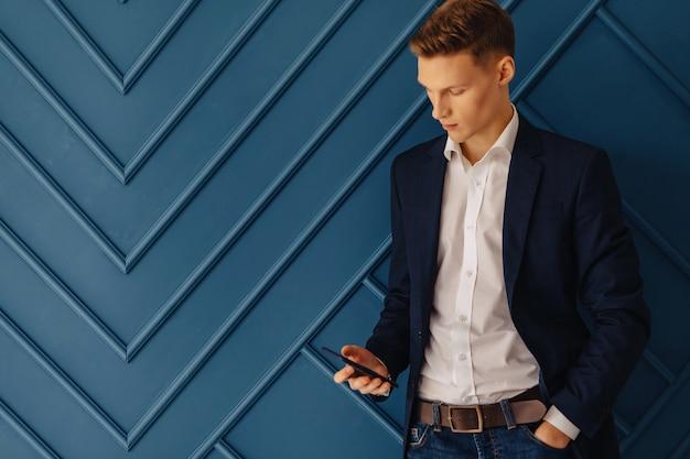 Chico joven con estilo con un teléfono, joven empresario, freelance
