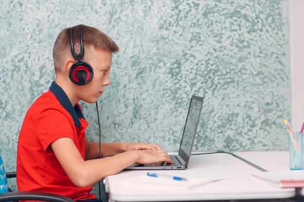 Chico joven estudiante con aprendizaje portátil