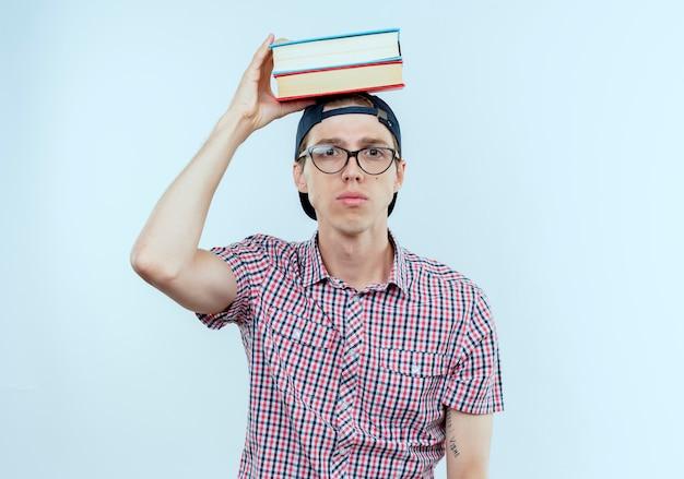 Chico joven estudiante con gafas y gorra poniendo libros en la cabeza.