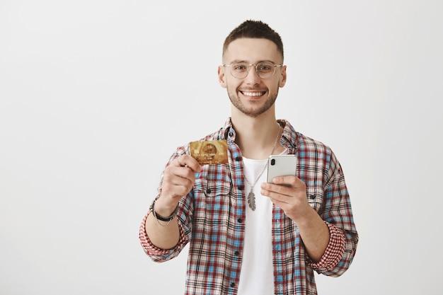 Chico joven feliz con gafas posando con su teléfono y tarjeta