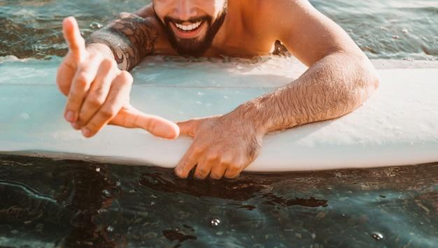 Chico joven feliz con gesto shaka acostado en tabla de surf en agua