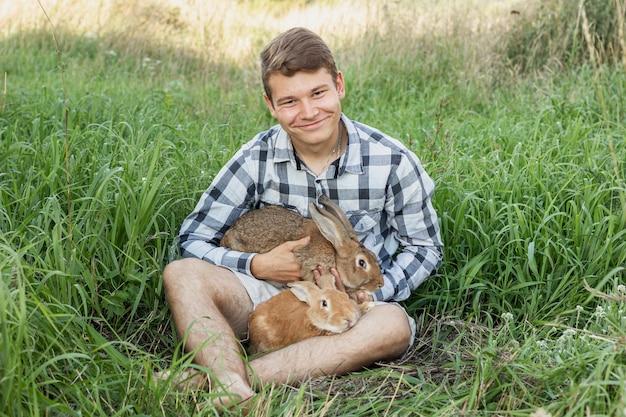 Chico joven en la granja con conejos