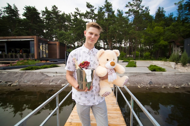 Un chico joven y guapo está esperando una reunión con su novia. esperando en el muelle con champaña y un oso de peluche. cita romántica.