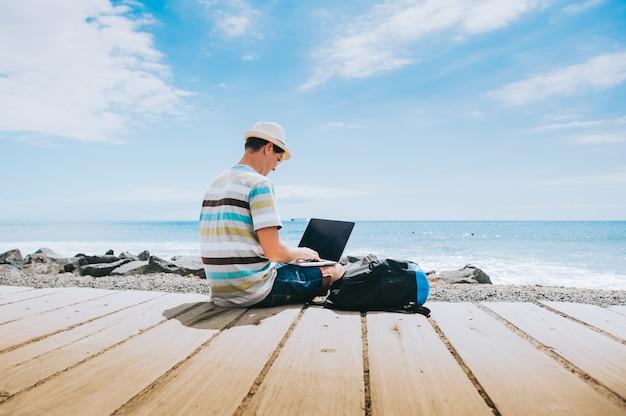 Chico joven y guapo el fotógrafo trabajando con una computadora portátil en la playa