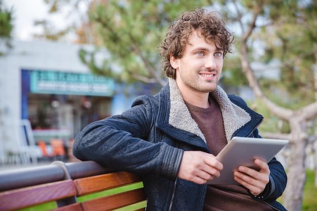 Chico joven guapo rizado positivo en chaqueta negra con tableta en el banco de madera en el parque y mirando a otro lado
