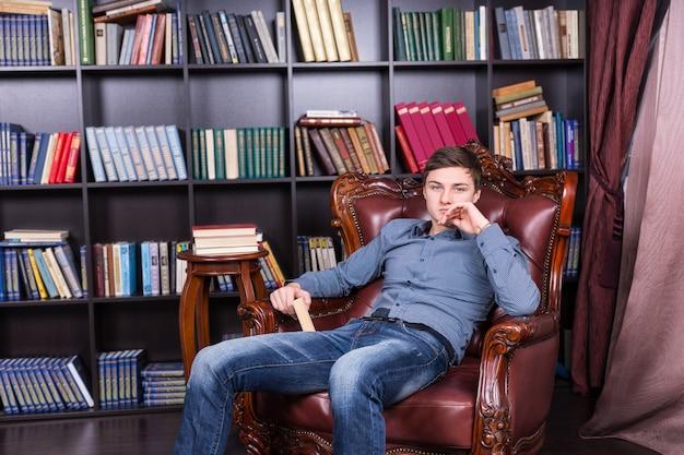Chico joven guapo en ropa de moda sentado en la silla de la biblioteca mientras sostiene un libro y mira a la cámara