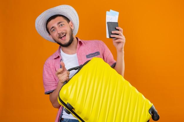 Chico joven guapo viajero con sombrero de verano con maleta y billetes de avión mirando a cámara salió y feliz sonriendo alegremente listo para viajar de pie sobre fondo naranja