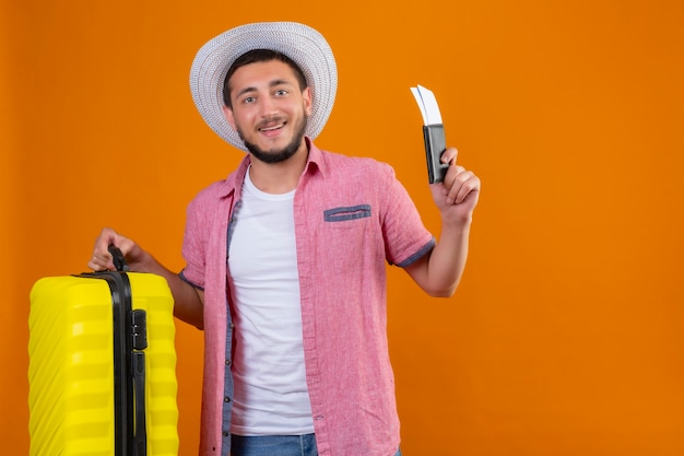 Chico joven guapo viajero con sombrero de verano con maleta y billetes de avión que parece seguro de sí mismo sonriendo alegremente listo para viajar de pie sobre fondo naranja