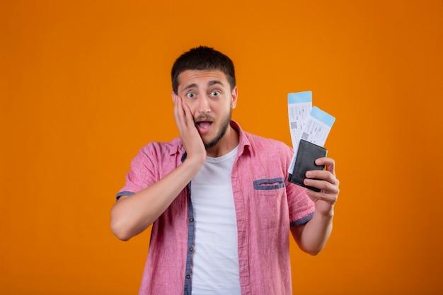 Chico joven guapo viajero sosteniendo billetes de avión mirando a cámara sorprendido y asombrado tocando su rostro con el brazo parado sobre fondo naranja