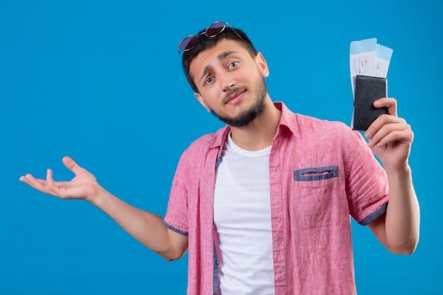 Chico joven guapo viajero sosteniendo billetes de avión mirando confundido de pie sobre fondo azul.