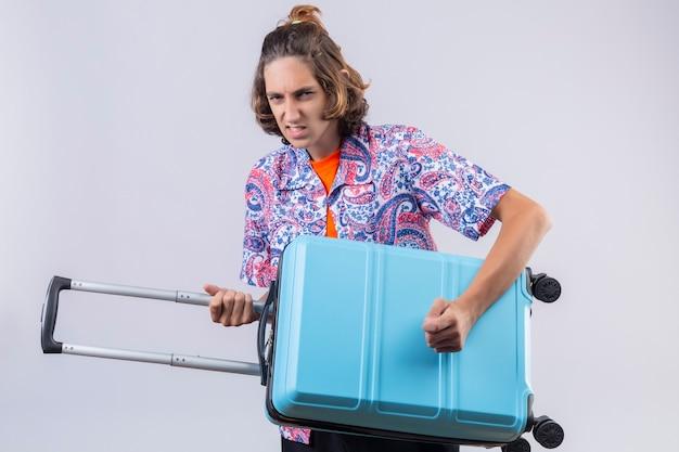 Chico joven guapo viajero sosteniendo la maleta usando como una guitarra mirando con expresión enojada de pie sobre fondo blanco.