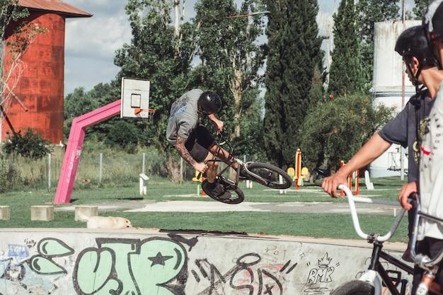 Chico joven haciendo trucos en el aire en bicicleta en el parque de patinaje