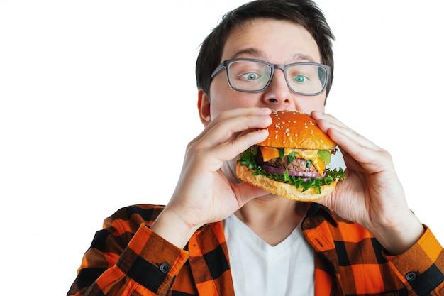 Un chico joven con una hamburguesa fresca.