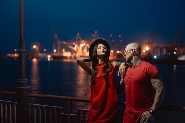 Chico joven y hermosa chica en el fondo del puerto nocturno