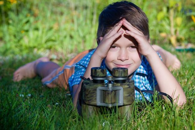 Chico joven investigador explorando con binoculares entorno en jardín verde