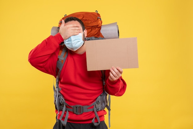 Chico joven con máscara médica con mochila y sosteniendo una hoja sin escribir poniendo la mano en los ojos sobre fondo amarillo aislado