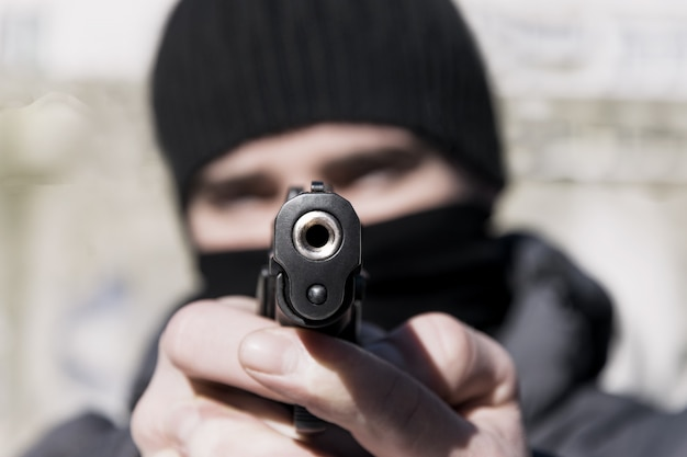 Un chico joven con una máscara con una pistola en sus manos. tonificado