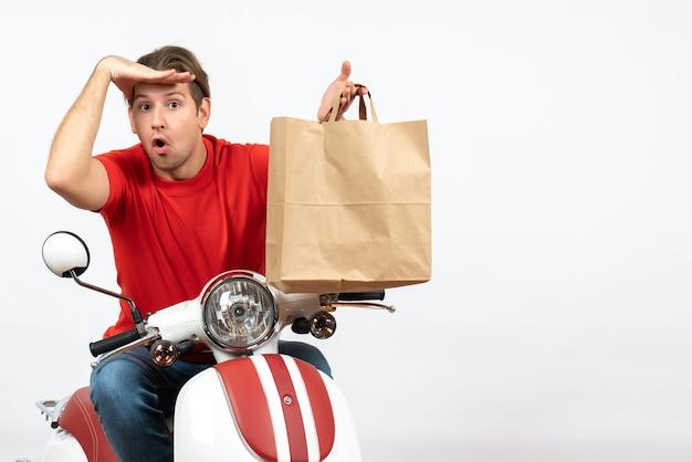 Chico joven mensajero concentrado ocupado en uniforme rojo sentado en scooter sosteniendo una bolsa de papel en la pared blanca