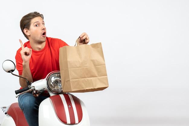 Chico joven mensajero curioso en uniforme rojo sentado en scooter sosteniendo una bolsa de papel apuntando hacia arriba en la pared blanca