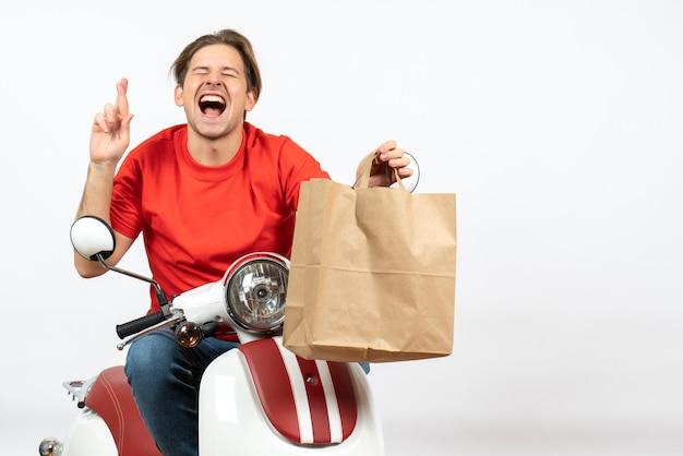 Chico joven mensajero emocional esperanzado en uniforme rojo sentado en scooter dando bolsa de papel en la pared blanca