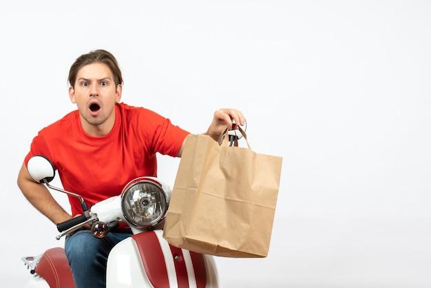 Chico joven mensajero emocional sorprendido en uniforme rojo sentado en scooter dando bolsa de papel mirando algo en la pared blanca