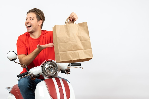 Chico joven mensajero feliz en uniforme rojo sentado en scooter sosteniendo una bolsa de papel en la pared blanca