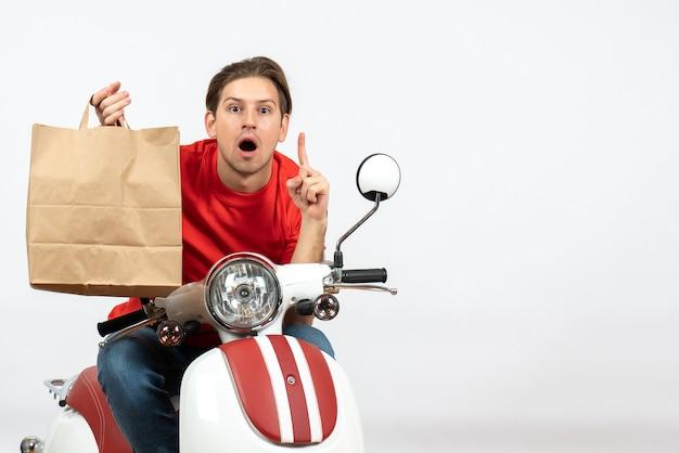 Chico joven mensajero sorprendido en uniforme rojo sentado en scooter sosteniendo una bolsa de papel apuntando hacia arriba en la pared blanca