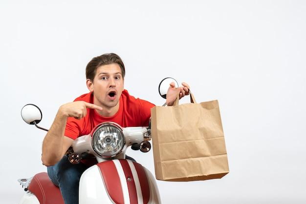 Chico joven mensajero sorprendido en uniforme rojo sentado en scooter sosteniendo una bolsa de papel en la pared amarilla