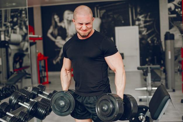 Un chico joven y musculoso en una camiseta negra se entrena en un gimnasio