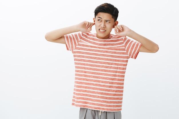 Un chico joven no puede concentrarse en la tarea porque escucha un ruido fuerte e irritante que viene de arriba apretando los dientes y frunciendo el ceño molesto, cerrando las orejas con los dedos índices