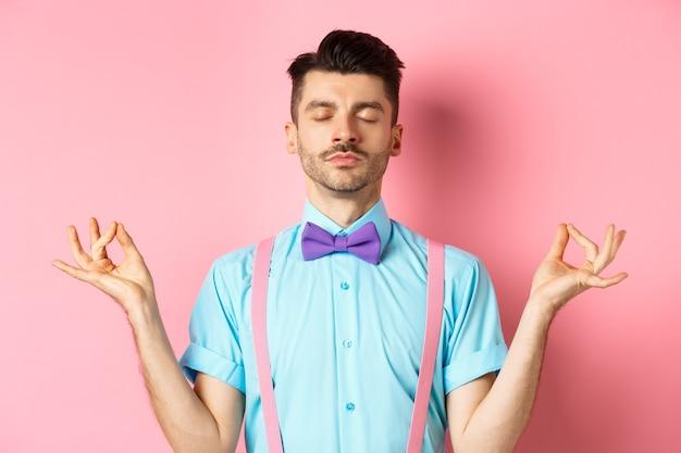 Chico joven en pajarita de pie tranquilo y pacífico, meditando con las manos en gesto mudra zen y ojos cerrados, practica yoga para relajarse, de pie sobre fondo rosa.